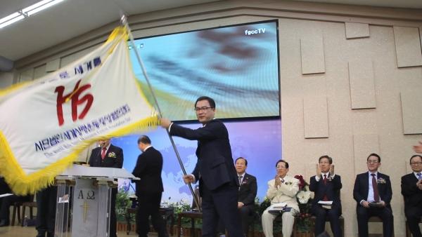 세계성령중앙협의회 제29대 대표회장 이수형 목사가 기를 흔들고 있다.