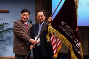 직전 세기총 대표회장 고시영 목사(왼쪽)가 세기총 깃발을 신임 대표회장 황의춘 목사(오른쪽)에게 넘겨주고 있다.