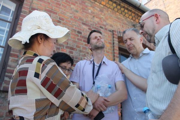아우슈비츠 강제수용소의 가이드를 위해서 폴리목사와 함께 순교자의 팀이 기도해 주는 모습