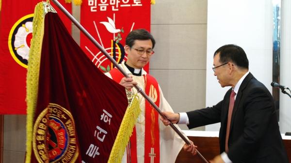 신임총회장 진영석 목사(왼쪽)가 직전총회장 김철환 목사로부터 총회기를 받고 있다.