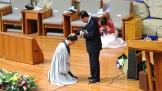 아버지 김삼환 목사(가운데 선 이)가 아들 김하나 목사(왼편 무릎 꿇은 이)에게 안수기도를 하고 있다.