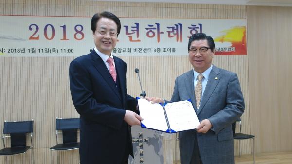 유중현 목사(오른쪽)가 직전대표회장 채영남 목사로부터 대표회장 당선증을 받고 있다.