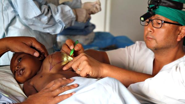사진2. 마다가스카르 이동진료 현장에서 혹이 난 아이를 치료중인 이재훈 의사