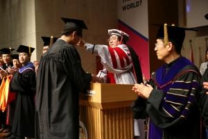 (사진5)장순흥 한동대 총장이 졸업생의 학사모 수술을 오른쪽에서 왼쪽으로 옮겨주고 있다