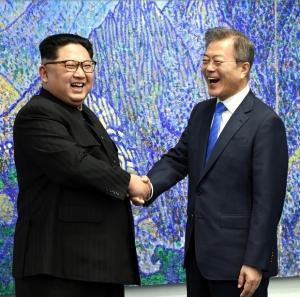 문재인 대통령과 김정은 국무위원장이 악수를 나누며 환하게 웃고 있다.