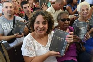 쿠바 성도가 성경을 받아 들고 활짝 웃고 있다.