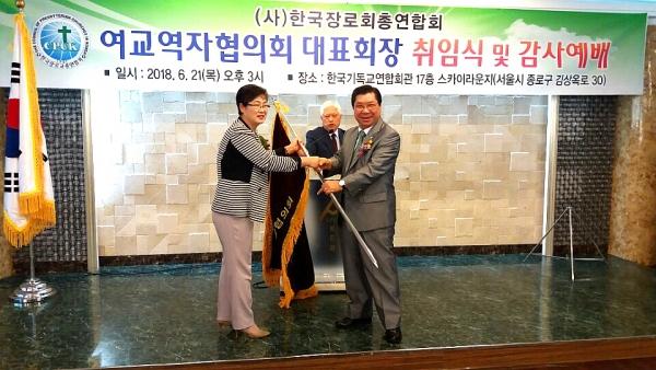 한장총 여교역자협 신임 대표회장 김희신 목사(왼쪽)가 대표회장 유중현 목사로부터 한장총기를 전달받고 있다.