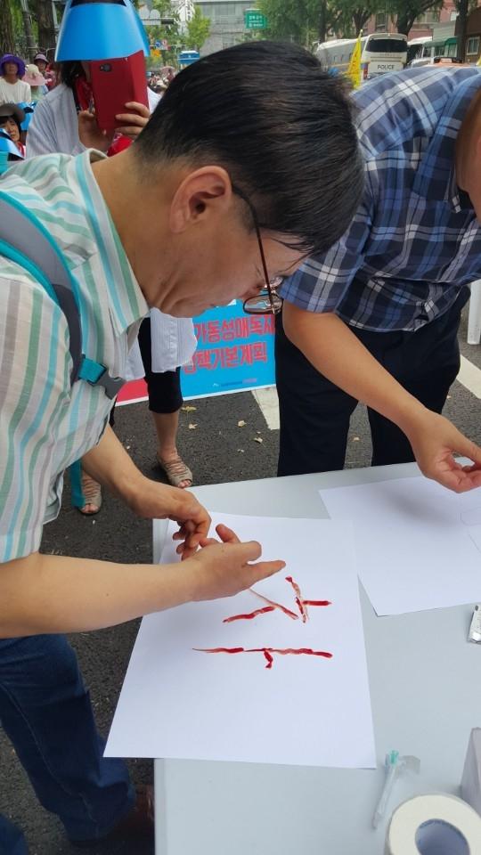동성애 동성혼 개헌 반대 국민연합(동반연)이 법무부가 국무회의 통과를 추진하고 있는 제3차 국가인권정책 기본계획(NAP)에 반대하며 26일 청와대 앞에서 집회를 개최한 가운데, 30여 명의 목회자들이 '혈서'로 NAP 폐지를 촉구했다.