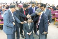 기침 교단 신임총회장 유관재 목사가 지방교회 교역자들과 순서자들로부터 축복기도를 받고 있다.