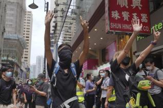 """홍콩 시내 중심가에서 24일 시위 참가자들이 중국의 홍콩 국가보안법 제정에 반대하는 시위를 벌이고 있다. 이들이 펼쳐 보이고 있는 다섯개 손가락과 한개의 손가락은 """"5대 요구 사항을 단 하나라도 빼지 말고 모두 이행하라""""는 뜻이다. 시위대의 5대 요구는 송환법 공식 철회, 경찰 강경 진압 책임자 문책, 시위대를 '폭도'로 규정한 입장 전면 철회, 체포된 시위대 석방, 행정장관 직선제 실시다."""