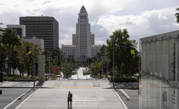 미국 캘리포니아 로스앤젤레스 그랜드애비뉴에서 3월19일 이동금지령이 내려진 가운데 한 시민이  텅빈 중심가를 걷고 있다. 개빈 뉴섬 캘리포니아주지사는  주 전역 이동 제한 명령을 내리고 예배등 다중 집회도 금지했다. ⓒ 뉴시스