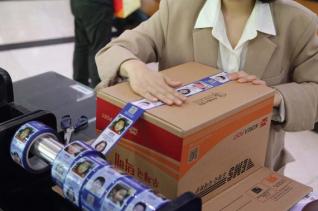 서울 강남 우체국에서 고객이 장기 실종아동 정보가 인쇄된 '호프테이프'를 이용해 택배 상자를 밀봉하고 있다. ⓒ제일기획