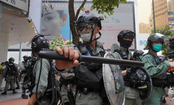 27일 홍콩 중심부에서 시위 진압 경찰이 시위대를 정리하기 위해 대열을 갖추고 있다. 중국 전국인민대표대회(전인대)가 처벌 대상을 대폭 확대하는 홍콩 국가보안법 수정안을 추진하는 가운데 홍콩 시위대는 입법부 청사 밖에서 이에 반대하는 시위를 벌이고 있다.