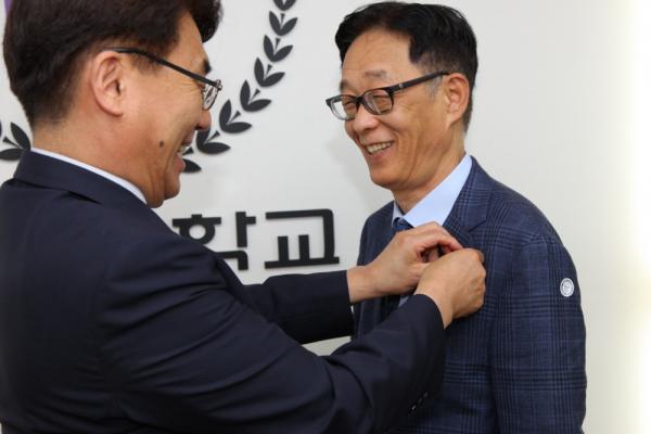 박상규 이사장(좌)이 권오성 초빙교수(우)에게 한신대 뱃지를 달아주고 있다.