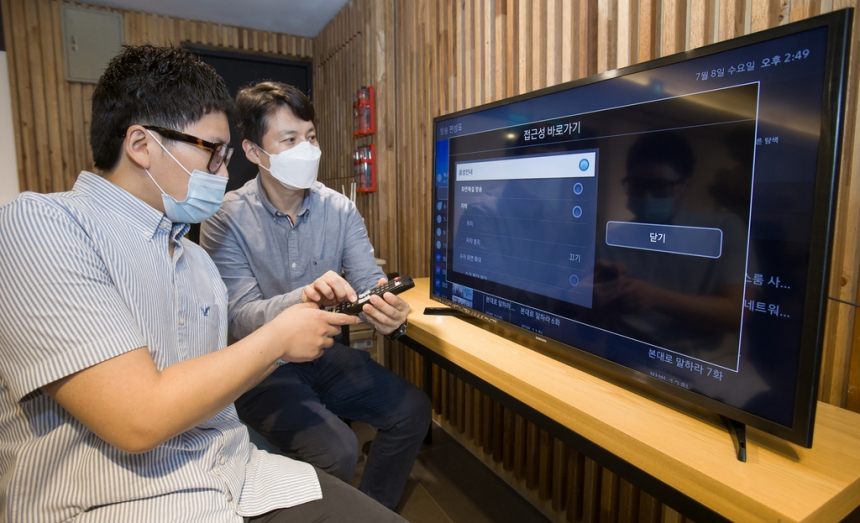삼성전자 상품전략팀 직원(오른쪽)이 서울 관악구에 위치한 실로암 시각장애인 복지관에서 한 시각 장애인에게 삼성전자 스마트TV의 접근성 기능에 관해 설명하고 있다.