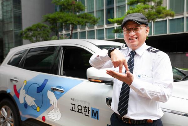 청각장애인 기사가 수어 아티스트 지후트리가 자립이라는 수어를 이미지화해 디자인한 고요한 M 차량 앞에서 자립이라는 의미의 수어를 하는 모습