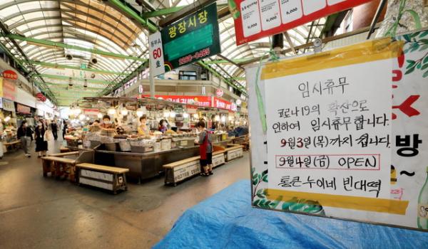 정부의 사회적 거리두기 2.5단계 시행 이후 첫 평일 점심시간인 31일 오후 서울 종로구 광장시장의 한 점포에 코로나19 확산으로 인한 임시휴무 안내문이 부착돼 있다.
