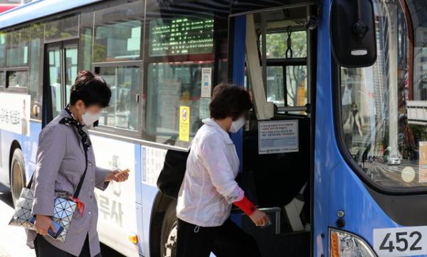 5일 서울 강남구 강남역 인근에서 시민들이 마스크를 쓰고 버스에 탑승하고 있다. 다음달 13일부터 마스크를 대중교통과 병원, 요양원, 집회시위장 등에서 쓰지 않으면 과태료 10만원이 부과된다.