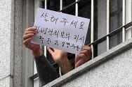 대규모 집단 감염이 발생한 서울 동부구치소에서 233명이 추가 확진돼 누적 확진자가 761명으로 집계된 29일 서울 송파구 동부구치소에서 한 수용자가 자필로 쓴 글을 취재진에게 보여주고 있다. 종이에는 '살려주세요 질병관리본부 지시 확진자 8명 수용'이라고 적혀있다.