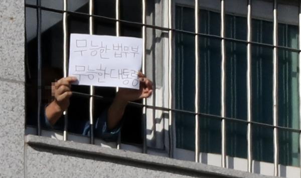 6일 서울 송파구 서울동부구치소에서 한 수용자가 종이에 쓴 글을 취재진에게 보여주고 있다.