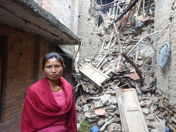 네팔의 무너진 건물 앞에 서 있는 성도