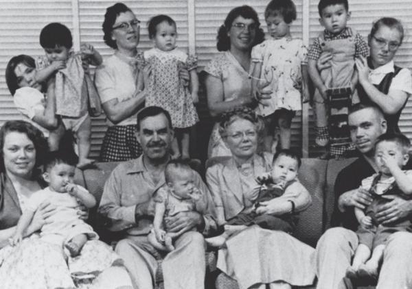 홀트 부부 가족이 한국에서 입양한 아이를 한 명씩 안고 기념촬영을 하고 있다.