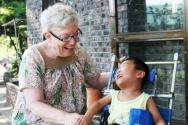 2006년 말리 홀트가 함께 생활하는 장애 아동과 마주 보며 활짝 웃고 있다.