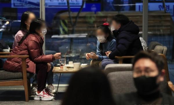 다중이용시설에 대한 집합금지·운영제한이 완화된 지난 19일 오후, 서울 마포구 홍익대학교 인근의 한 프렌차이즈형 카페에서 마스크를 착용한 시민들이 커피를 마시고 있다. ⓒ뉴시스