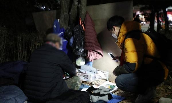 서울역희망지원센터 야간상담조 관계자가 17일 서울 중구 서소문역사공원에 있는 노숙인과 대화하고 있다.