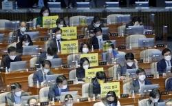 정의당 의원들이 26일 서울 여의도 국회 본회의에서 가덕도 관련 법안을 비판하는 피켓을 의석에 붙여 놓고 있다.