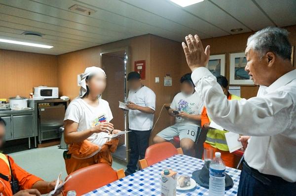 동아시아 A국 선원들에게 복음을 전한 후 기도하고 있는 김윤규 목사(맨 오른쪽).