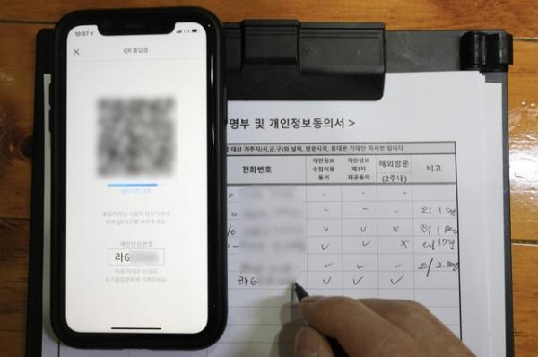 한 시민이 19일 오전 서울 시내의 한 식당에서 개인안심번호를 적고 있다. 이날부터 식당과 카페 등을 방문하면 수기 출입명부에 휴대전화 번호 대신 개인 정보가 보이지 않는 개인안심번호를 적을 수 있다.