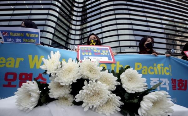 한국YMCA연합회 회원들이 19일 오후 서울 종로구 일본 대사관 앞에서 열린 후쿠시마 오염수 해양 방류 결정 규탄 기자회견에서 국화를 들고 있다.
