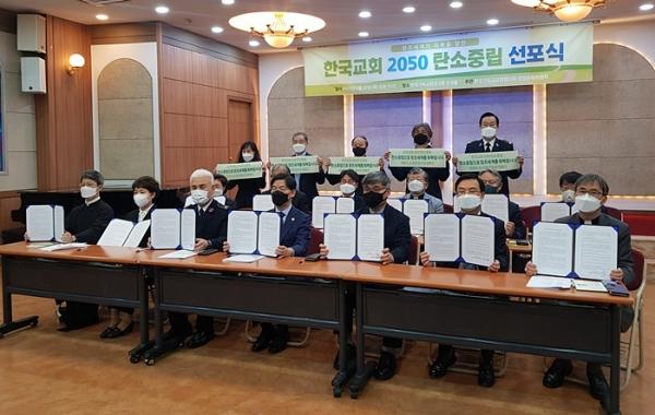 '한국교회 2050 탄소중립 선포식'에서 교단 및 연합기관 관계자들이 탄소중립을 선언하는 선언문과 플랜카드를 들고 있다.