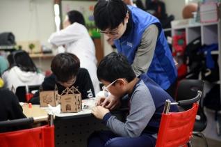 2019년 삼성SDI 푸른별 미래과학학교에 참여한 아동이 삼성SDI 임직원 강사와 함께 과학 실험을 하고 있다.