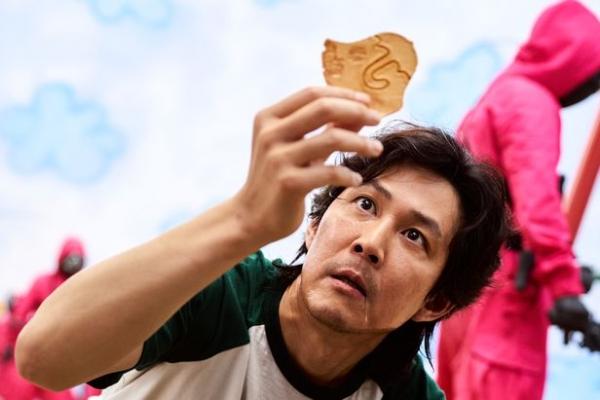 넷플릭스 드라마 '오징어게임' 중 달고나 게임에 몰입하고 있는 주인공의 모습.